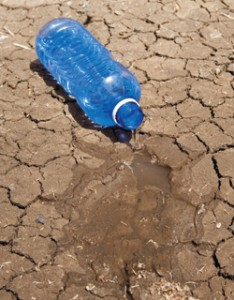 Water bottle spililng onto parched dry ground