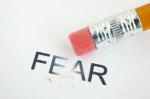 The word fear on a paper and a pencil erasing it.